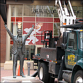 On the other end of Rice Park, the statue of hockey coach Herb Brooks is oveshadowed by a crane adding decorative lights outside RiverCentre, which will house media operations.