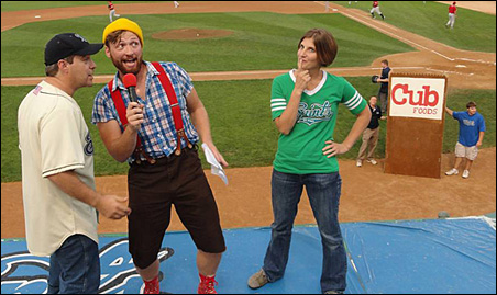 """The Saints' Lumberjack, conferring with Midway public address announcer Joe Wiener,  has quite a surprise for Krissy Haltinner during a """"What's in the Bag?"""" promotion at Friday's game."""