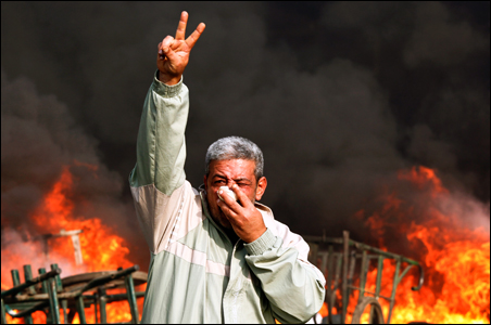 A protester gestures in front of a burning barricade during a demonstration in Cairo.