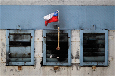 An inmate waves a Chilean flag from inside San Miguel public prison, after a fire broke out in the building, killing 81 inmates, in Santiago.