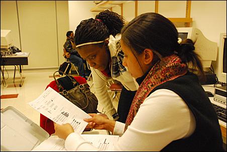 Admission Possible coach Jae Jae Brooks, right, walks through ACT exam scores with Roosevelt junior Ruth Ifonlaja.