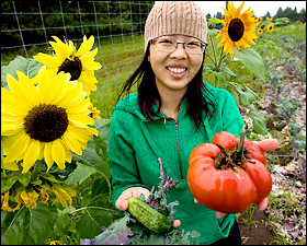 May Lee's daughter Mhonpaj shows off some of the fresh veggies from her family's farm operation at the Minnesota Food Association.