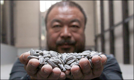 Ai Weiwei poses with his installation at Tate Modern