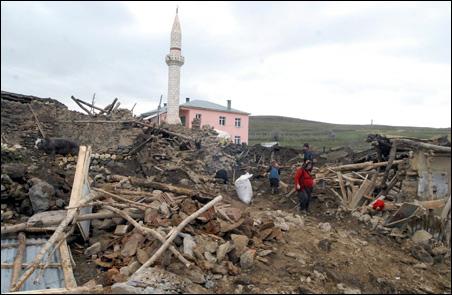 People walk around a destroyed house in Okcular Village, in Elazig province on Monday.