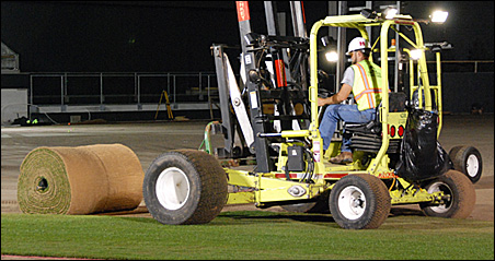 Workers Monday night put in place the first truckload of sod at Target Field.