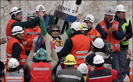 Mario Gomez, 63, the oldest of the 33 trapped miners, celebrates as he arrives on the surface as the ninth to be rescued on Wednesday.