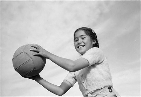 Girl and volley ball, Manzanar Relocation Center, California, 1943, by Ansel Adams