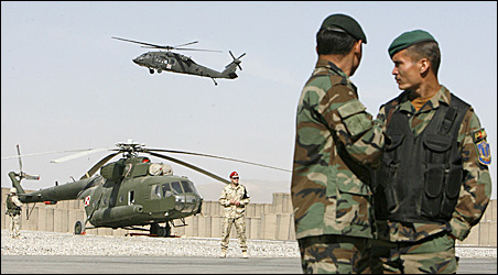Afghan army soldiers watch as a U.S. helicopter flies over a Polish helicopter at a military base in Ghazni province, Monday, Oct. 26, 2009.