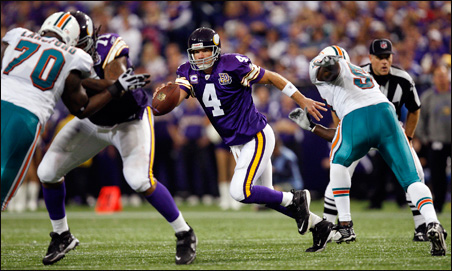 Brett Favre scrambles away from defensive pressure by Miami Dolphins linebacker Tim Dobbins, right, during the third quarter.