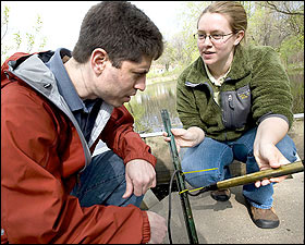 William Arnold,left, and Chris Wennen, a graduate student in water resources science, examine water monitors at a weir on a stormwater pond.