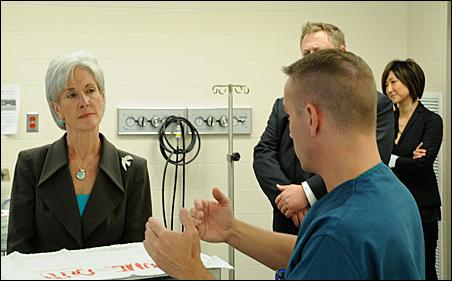 Secretary Kathleen Sebelius listens to Dr. Gary Collins, a trauma surgeon, during a tour of Regions Hospital.