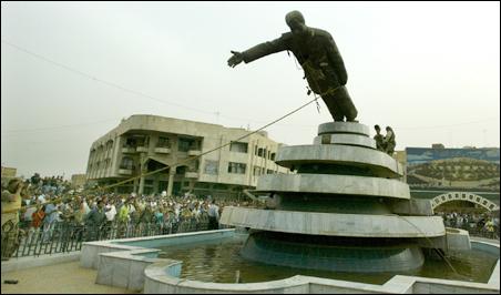 U.S. soldiers and Iraqi citizens pull down a statue of Iraqi President Saddam Hussein.