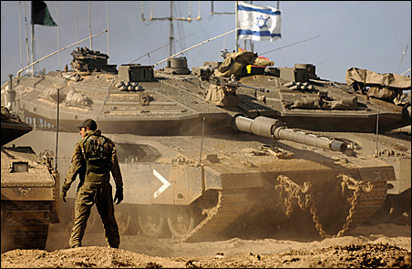 An Israeli soldier directs tanks near Kibbutz Nahal Oz, just outside the northern Gaza Strip, on Tuesday.