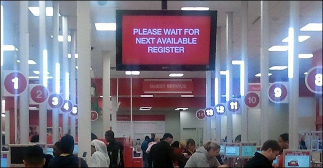 The Target store test includes an overhead sign that directs customers to cashiers.