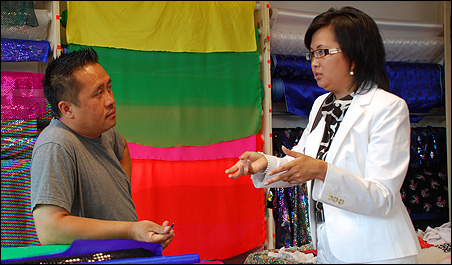 LRT outreach coordinator Shoua Lee, right, talking with a University Avenue business owner about the project.