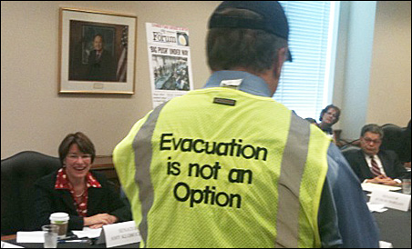 "Sens. Amy Klobuchar and Al Franken look on as Fargo Deputy Mayor Tim Mahoney, wearing a vest with the words ""Evacuation is not Option"" emblazoned, on Monday describes flood preparation efforts in Fargo and Moorhead."