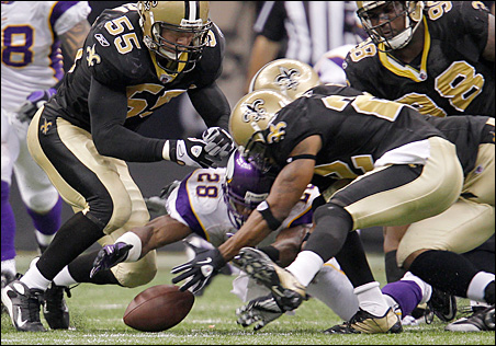 Vikings runningback Adrian Peterson dives to recover his fumble against Saints cornerback Tracy Porter and linebacker Scott Fujita in the third quarter.