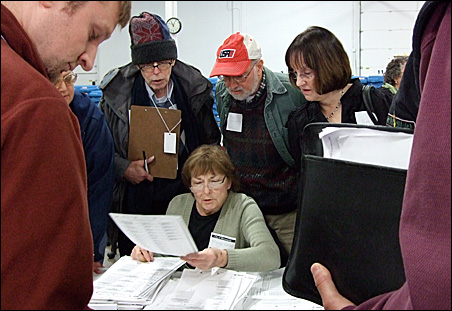 Gathered in a cold warehouse, bundled-up observers watch intently as an election judge prepares Minneapolis ballots for the recount.