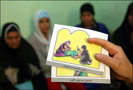 A counselor holds up cards used to educate women about female genital mutilation (FGM) in Minia, Egypt.