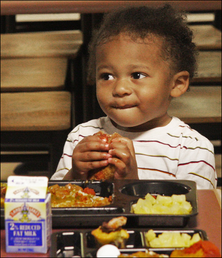 Two-year-old Gabriel Ellis enjoys a bite of meat loaf during lunch in the People Serving People family shelter cafeteria.