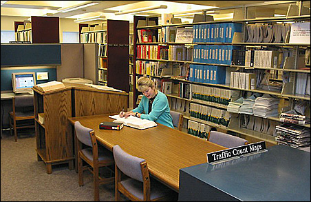 An unidentified customer takes notes at the Mn/DOT Library.