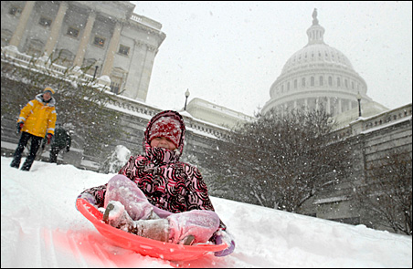Sledders play in the snow on the West Front of the U.S. Capitol in Washington on Saturday.
