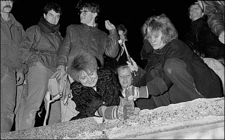 Berliners take a hammer and chisel to a section of the Berlin Wall in front of the Brandenburg Gate after the opening of the East German border was announced in Berlin, November 9, 1989.