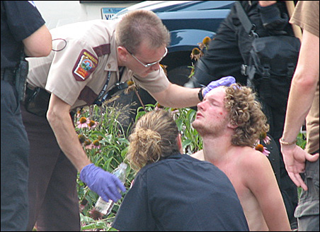 Police offer water to a detained protester at Minnesota Street and Kellogg Boulevard in downtown St. Paul.