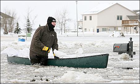 Troy Kind of Dilworth, Minn., uses a canoe to move sandbags through an Oxbow, N.D., housing development.