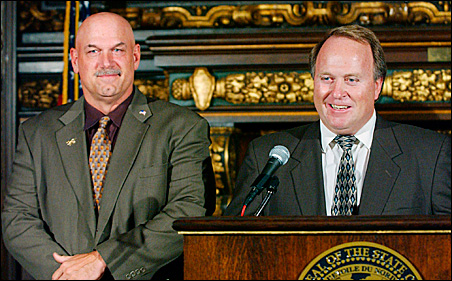 Then-Gov. Jesse Ventura, left, listens as Dean Barkley talks to reporters at the Capitol in St. Paul in 2002.