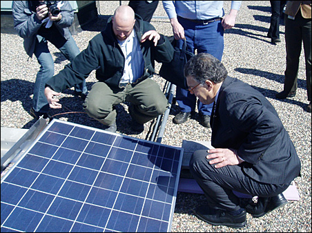 Sen. Franken inspects the solar panels installed on the roof of Mulroy's Body Shop.