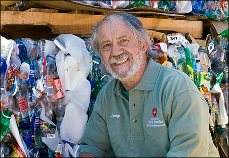 Poet Larry Schug poses next to piles of sorted recycling -- the labor of his days -- at the College of St. Benedict.