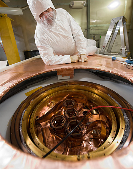 A scientist observes detectors set up to interact with particles from dark matter.