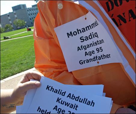 Some demonstrators wear cards naming U.S. detainees.