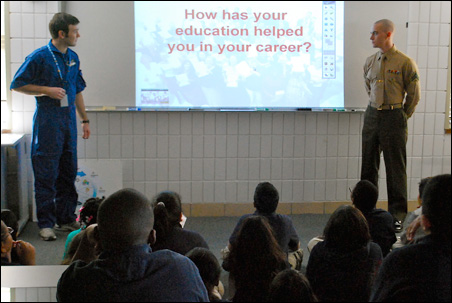 Members of the military speak to students and answer questions.