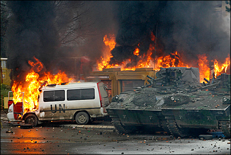 French NATO peacekeeping vehicles burn during clashes Monday with Serb protesters in the ethnically divided city of Mitrovica.