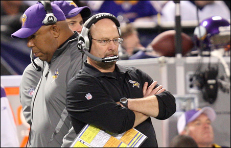 Brad Childress watches Sunday's game as quarterback Brett Favre, background in center, leans against an equipment crate during the third quarter.