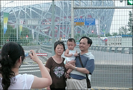Thousands gather every night to be near the Bird's Nest and to be photographed with loved ones.
