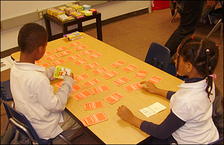 Playing a card game to improve memory and concentration are Jordan Gwaltney, 7, and Favor Osojuri, 5.