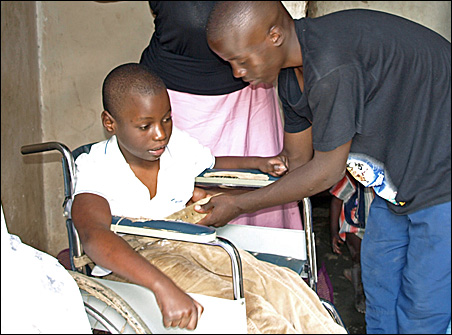 A family member helps Mariam in her wheelchair.