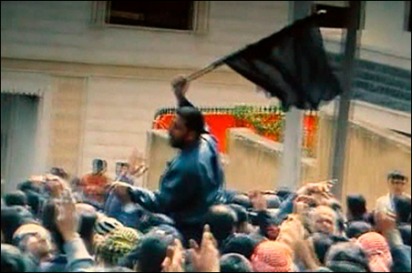 This still image from amateur video shows a mourner waving a flag amongst the crowds taking part in the funerals of protesters killed in earlier clashes in Deraa.