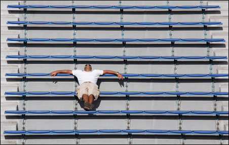 A fan rests in the stands at the Louis Armstrong Stadium during the match between Amelie Mauresmo of France and Tatjana Malek of Germany at the U.S. Open tennis championship in New York, Aug. 31, 2009.