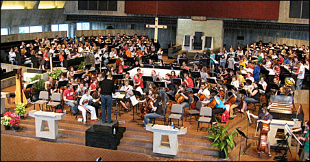 """Lee Nelson conducts a rehearsal of """"To Be Certain of the Dawn"""" this week at the Abbey Church at St. John's University in Collegeville."""