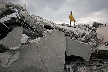 A member of the Polish Urban Search and Rescue team stands on the roof of a destroyed house that overlooks Port-au-Prince.