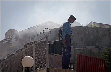 A policeman stands on the walls of the U.N. World Food Programme offices in Islamabad as smoke rises from the aftermath of a suicide bomb attack inside the compound Monday, Oct. 5, 2009.