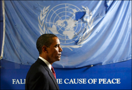 President Barack Obama passes by a battered United Nations flag that flew over the bombed Canal Hotel in Iraq at the United Nations Headquarters in New York, Wednesday, Sept. 23, 2009.