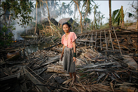 A woman sifts through the debris of her home destroyed by Cyclone Nargis near Kunyangon May 9.