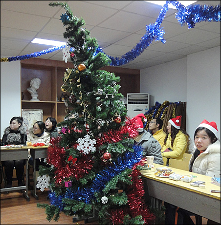 Staff, students and their families enjoy a Christmas party in an art classroom at Shanghai Putuo Spare Time University.