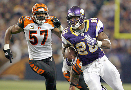 Adrian Peterson, right, rushes for a gain and first down past Cincinnati Bengals linebacker Dhani Jones during the second quarter.