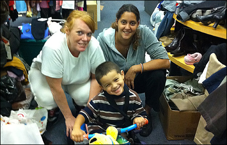 Setting up Families Helping Each Other in a new space are volunteers Jennifer Doherty, left, who is the warehouse manager, and Sarah Clay and son Manny, 3.